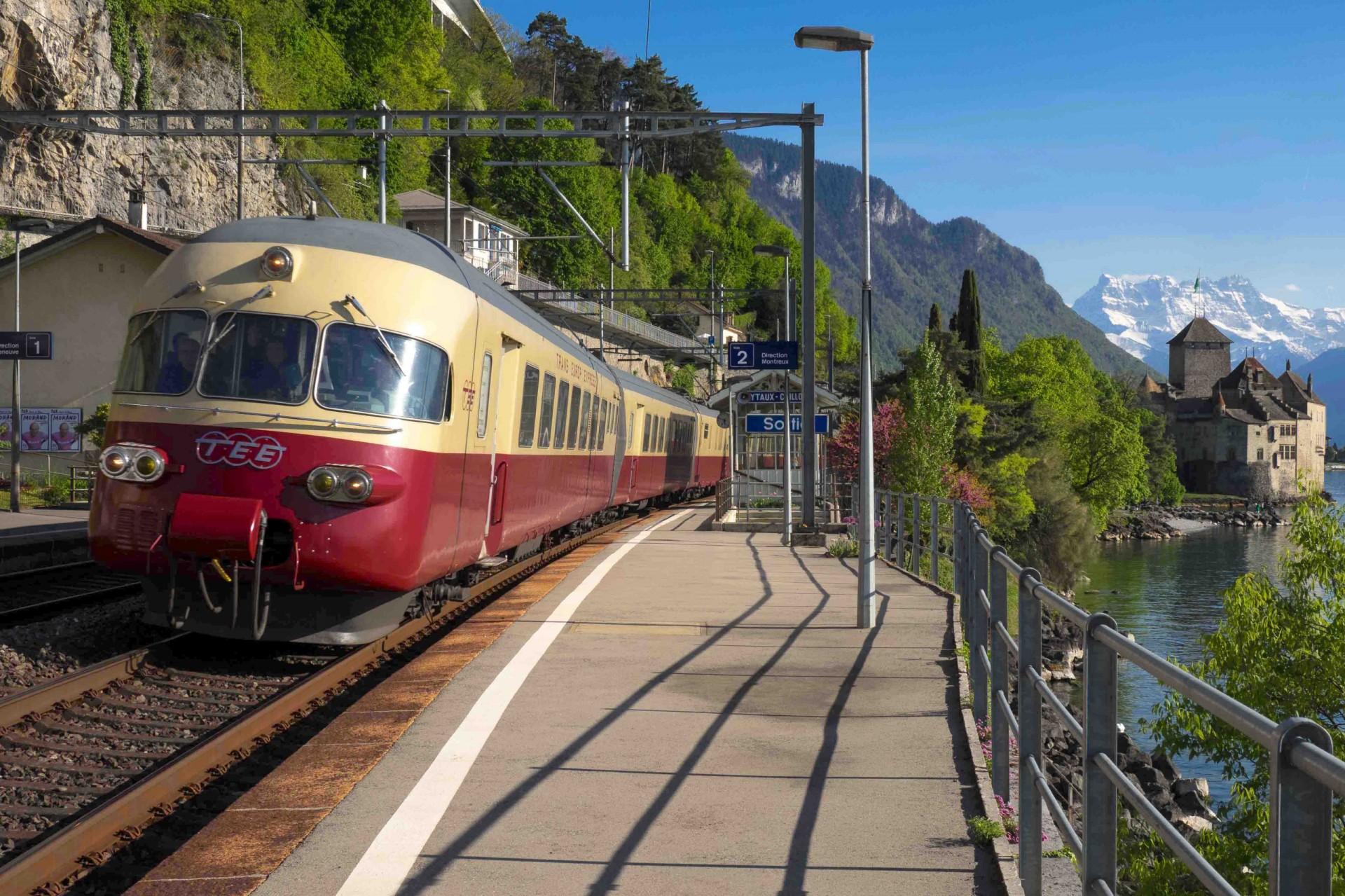 A preserved RAe TEE II trainset passing through Veytaux-Chillon station, on the Cisalpin's route (but not a stop), with Chillon Castle in the background MARKUS EIGENHEER (WIKIPEDIA)