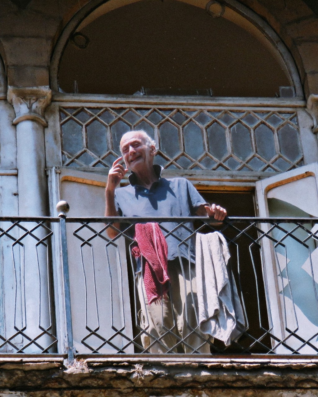 An elderly man stares out of his balcony onto the street of Gemmayze, where civilian volunteers cleaned the streets from the debris, on August 6, 2020. Photo by Hadil Dia (mindshapedbox)